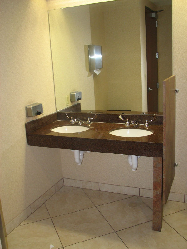 A Commercial ADA Vanity With Granite Top Equiped With A Blade Handle  Controlled Faucet And Undermount Sink Showing Insulated Plumbing In ADA  Restroom
