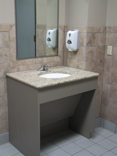 Commercial ADA vanity with removable panel for plumbing access in Austin, Texas.