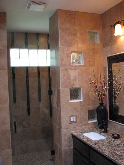 A bathroom remodel showing a walk in shower accented by a glass block design and fine cabinetry.