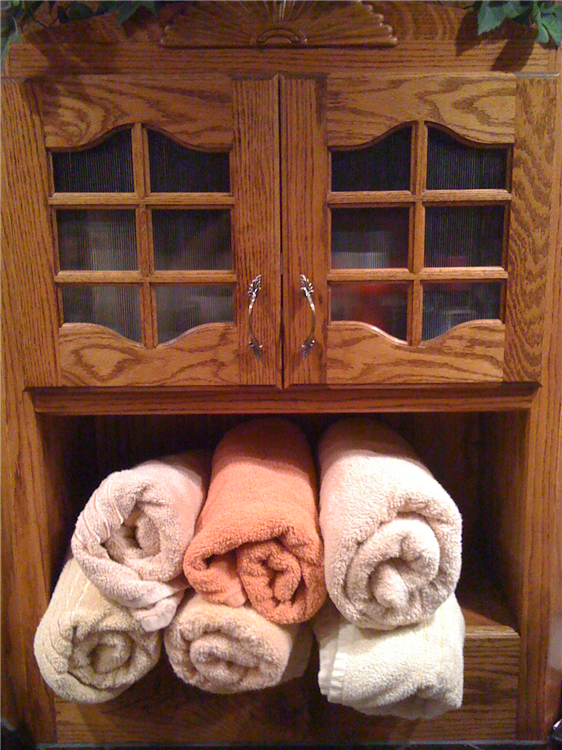 A Custom Stained Red Oak Linen Cabinet With Glass Inserts and Bath Towel Rolls