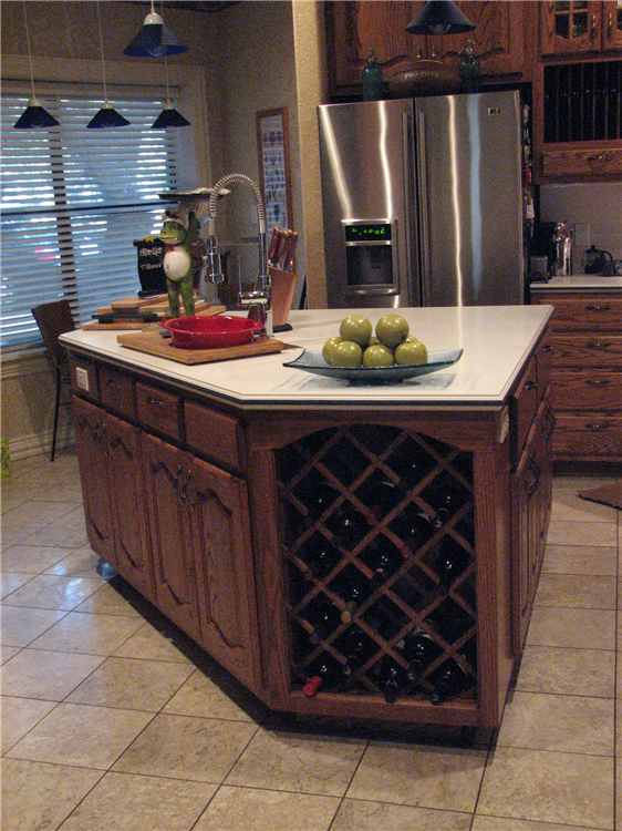 Custom Stained Oak Cabinets With Raised Panel Doors Below a Solid Surface Top