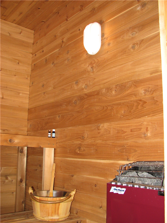 A Custom Dry Sauna Room With Natural Cedar Benches and Walls