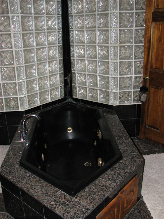A Custom Jetted Tub Seated in Granite and Pushed Back into a Glass Block Light Shaft